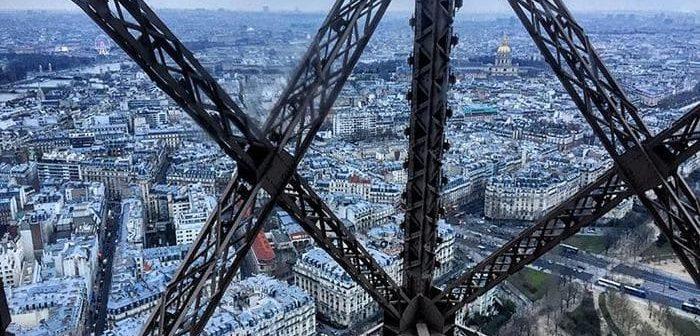 Vue de Paris à travers la structure de la Tour Eiffel